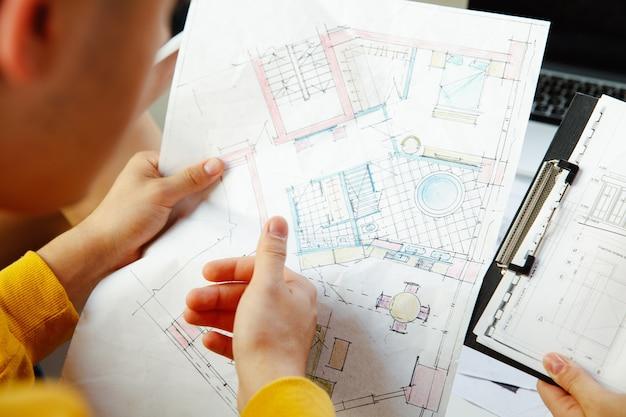 Innenarchitekt, der mit jungem paar arbeitet. schöne familie und professioneller designer oder architekt, der das konzept des zukünftigen interieurs bespricht und mit farbpalette, raumzeichnungen im modernen büro arbeitet.