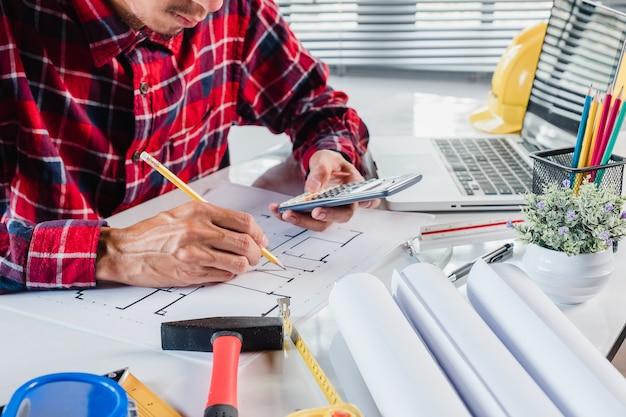Innenarchitekt des geschäftsmannes, der daten mit taschenrechner und architectura bearbeitet und bespricht