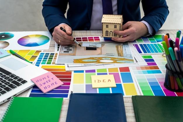 Innenarchitektenhand, die mit illustrationsskizze, farbschema des materials, des notizbuchs und des materials arbeitet. konzept der renovierung, reparatur oder dekoration von häusern