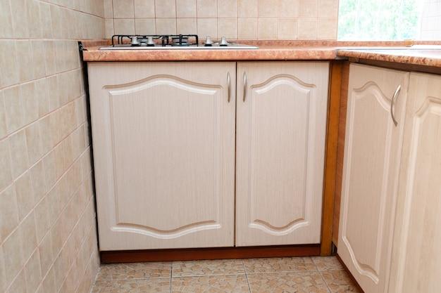 Innenarchitektur der modernen schmalen, intelligenten kompaktküche mit weißen zeitgenössischen möbeln, beigefarbenen keramikfliesen an der wand, gasherd und fensteransicht.