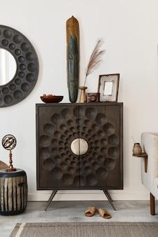 Innenarchitektur des ethnischen wohnzimmers mit moderner kommode, rundem spiegel, dekoration, möbeln und persönlichen accessoires. weiße wand.