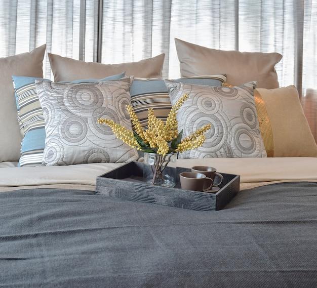 Innenarchitektur des luxusschlafzimmers mit gestreiften kissen und dekorativem teesatz auf bett
