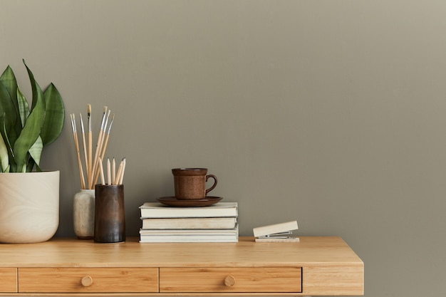 Innenarchitektur des neutralen böhmischen wohnzimmers mit stilvollem schreibtisch, buch, tasse, pflanze, bürobedarf, uhr, kopienraum, notizen und persönlichem zubehör.
