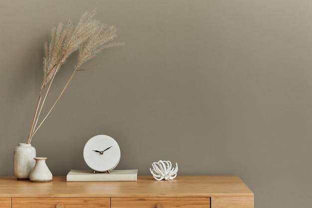 Innenarchitektur des neutralen böhmischen wohnzimmers mit stilvollem schreibtischsessel getrocknete blumen buchdekoration bürobedarf kopie raum notizen uhr und persönliches zubehör