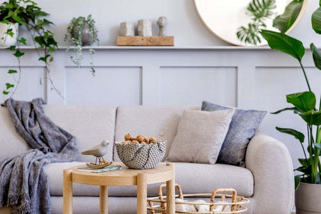 Innenarchitektur des skandinavischen wohnzimmers mit stilvollem grauem sofa, couchtisch, tropischer pflanze, spiegel, dekoration, kissen, plaid und eleganten persönlichen accessoires in moderner wohnkultur.