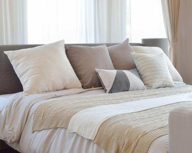 Innenarchitektur des stilvollen schlafzimmers mit braun gemusterten kissen auf bett und dekorativer tischlampe.
