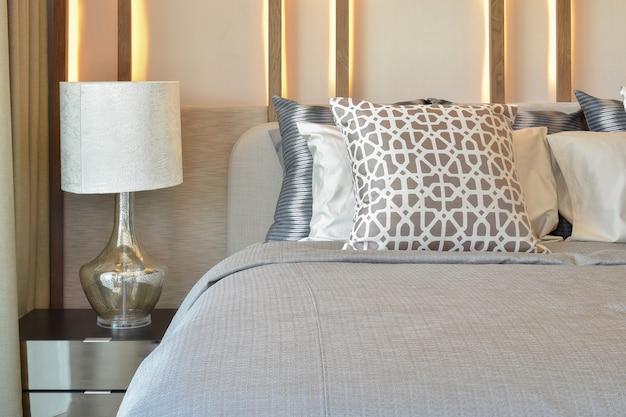 Innenarchitektur des stilvollen schlafzimmers mit braunen kissen auf bett und dekorativer tischlampe.