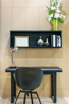 Innenarchitektur für arbeitsbereich mit lampe auf schwarzem spitzenschreibtisch