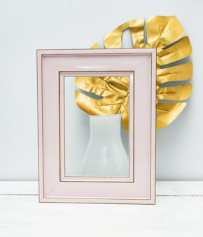 Innenarchitektur. leerer rosa fotorahmen und monsterblatt in weißer vase auf weißem wandhintergrund.