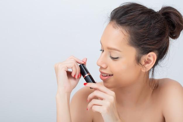 Innenatelieraufnahme für die schöne asiatin, die lippenstift breit anwendend lächelt