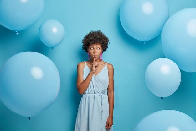 Innenaufnahme der afroamerikanischen dame drückt zeigefinger an die lippen, zeigt schweigeschild, erzählt geheimnis, verbreitet gerüchte und schaut zur seite, verbringt freizeit auf gesellschaftlichen ereignissen trägt kleid, alles in blauer farbe