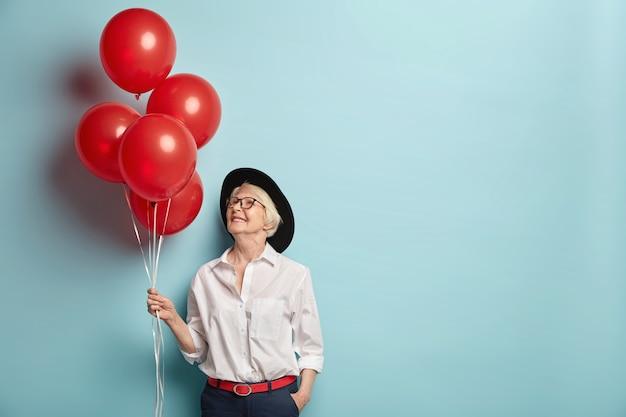 Innenaufnahme der angenehm aussehenden fröhlichen frau des alters hält helium-luftballons, kommt auf party für ältere menschen, um ihrer besten freundin zu gratulieren, konzentriert oben, trägt modische kleidung