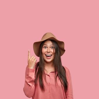 Innenaufnahme der angenehm aussehenden zufriedenen freundin zeigt mit dem zeigefinger nach oben, zeigt freien platz, lächelt positiv