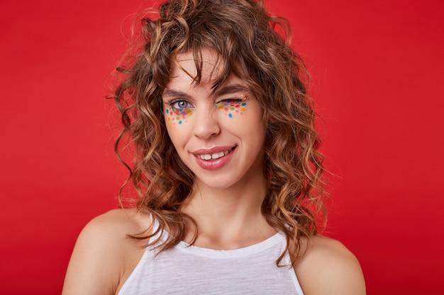 Innenaufnahme der attraktiven jungen frau mit dem schönen lächeln, das erfreut aussieht, ein augenzwinkern gibt, steht und freizeitkleidung trägt