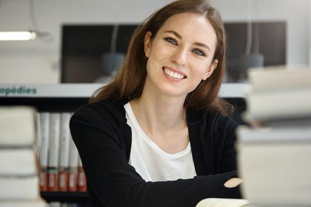 Innenaufnahme der attraktiven kaukasischen teenagerfrau mit langen dunklen haaren, die am schreibtisch mit vielen lehrbüchern sitzen