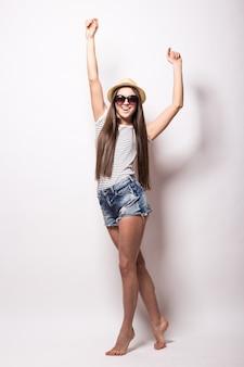 Innenaufnahme der freudigen jungen europäischen frau gibt vor zu tanzen, trägt modische bluse, hut und shorts, erholt sich während der sommerzeit