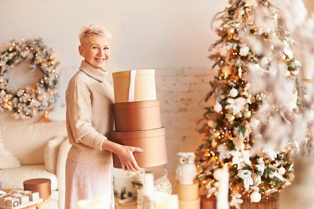 Innenaufnahme der fröhlichen eleganten frau mittleren alters mit blonden kurzen haaren, die im dekorierten wohnzimmer stehen, das kisten mit geschenken trägt und sie bis weihnachten versteckt. frohes neues jahr-konzept
