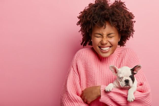 Innenaufnahme der glücklichen dunkelhäutigen frau hält schläfrigen welpen der französischen bulldogge, schließt die augen, hat ein breites lächeln, trägt lässigen pullover