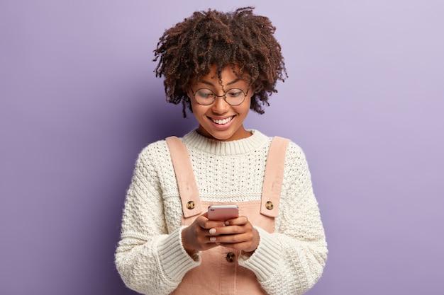 Innenaufnahme der glücklichen lockigen frau mit erfreutem gesichtsausdruck, liest nette nachricht vom freund, konzentriert im smartphone