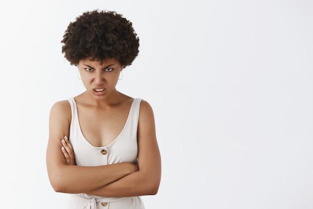 Innenaufnahme der hasserfüllten wütenden jungen afroamerikanerfrau mit dem lockigen haar, das unter der stirn mit wut und verachtung schaut, die hass und empörung ausdrückt, die hände auf der brust gekreuzt halten, verächtliche person