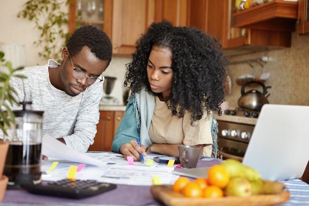 Innenaufnahme der jungen afrikanischen familie, die ihre finanzen analysiert