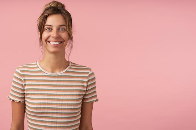 Innenaufnahme der jungen attraktiven braunhaarigen frau mit lässiger frisur, die ihre weiße perfekte tetth zeigt, während sie gern in die kamera schaut und über rosa hintergrund steht