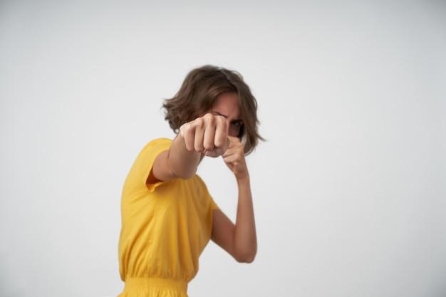 Innenaufnahme der jungen brünetten frau mit lässigem frisurboxen mit erhobenen fäusten im stehen, kampfbereit, gelbes t-shirt tragend