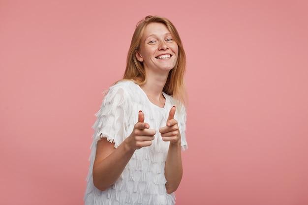 Innenaufnahme der jungen glücklichen rothaarigen frau mit natürlichem make-up, das auf kamera mit erhöhten zeigefingern zeigt und fröhlich lächelt, während sie über rosa hintergrund aufwirft