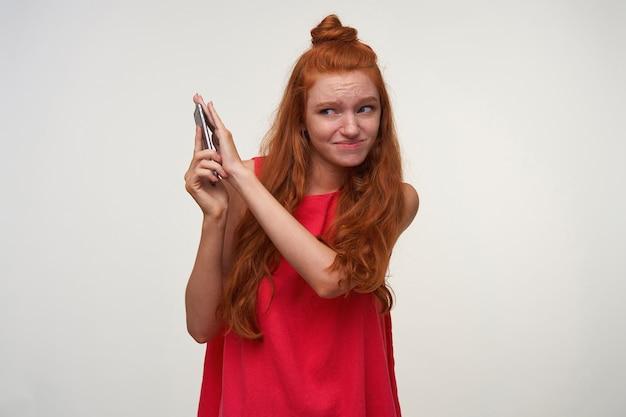 Innenaufnahme der jungen lesekopffrau, die ihr haar im knoten trägt, über weißem hintergrund im lässigen kleid aufwirft, unangenehmes gespräch mit ihrem smartphone hat und mobilteil abdeckt, um geräusche zu vermeiden