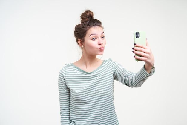 Innenaufnahme der jungen reizenden braunhaarigen dame mit brötchenfrisur, die ihre lippen schmollt, während schuss von sich selbst macht und smartphone in der erhobenen hand hält, isoliert über weißer wand