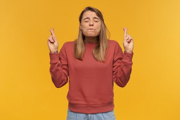 Innenaufnahme der jungen studentin mit gekreuzten fingern hält ihre augen geschlossen