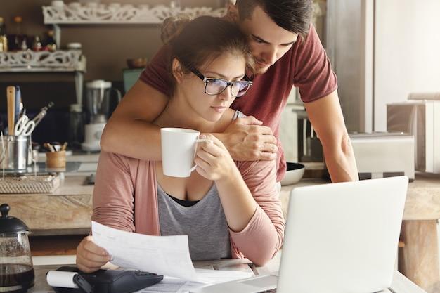 Innenaufnahme der jungen unglücklichen kaukasischen familie, die finanziellem stress gegenübersteht. schöne frau, die eine brille trägt, die tee trinkt, während sie papierkram mit ihrem ehemann tut, der hinter ihr steht und sie umarmt
