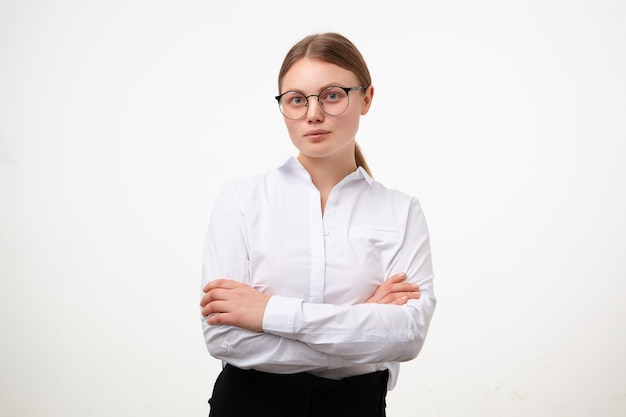Innenaufnahme der jungen weißköpfigen frau in der brille, die ihre hände auf der brust gekreuzt hält, während sie ruhig in die kamera schaut und über weißem hintergrund in formellen kleidern aufwirft