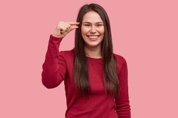 Innenaufnahme der lächelnden frau zeigt wenig von etwas, gesten mit der hand, in hochstimmung