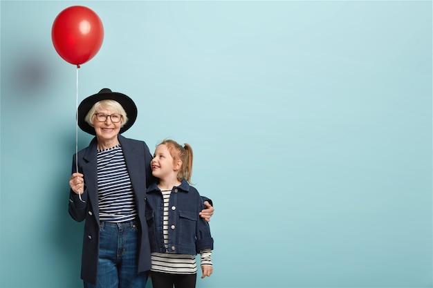 Innenaufnahme der modischen älteren frau umarmt kleines kind, genießen sie, zeit zusammen zu verbringen