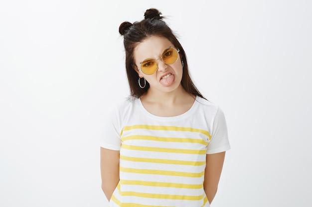 Innenaufnahme der modischen jungen frau, die mit sonnenbrille gegen weiße wand aufwirft