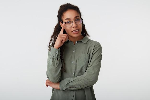 Innenaufnahme der positiven jungen braunhaarigen lockigen frau mit dunkler haut, die erhobene hand auf ihrer brille hält, während über weißem hintergrund im grünen hemd aufwirft