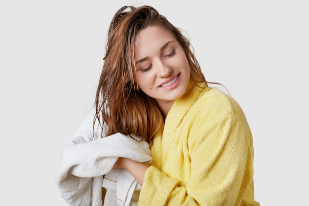 Innenaufnahme der schönen frau wischt nasses haar mit handtuch, gekleidet im gelben bademantel