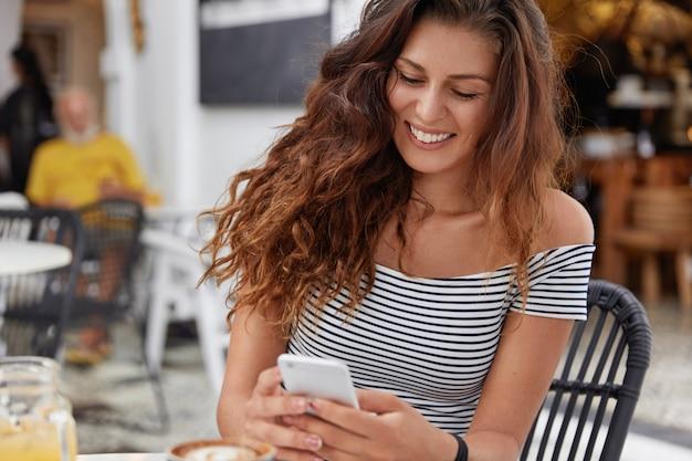 Innenaufnahme der schönen glücklichen frau gekleidet in gestreiftem t-shirt, liest lustige sms-nachricht,