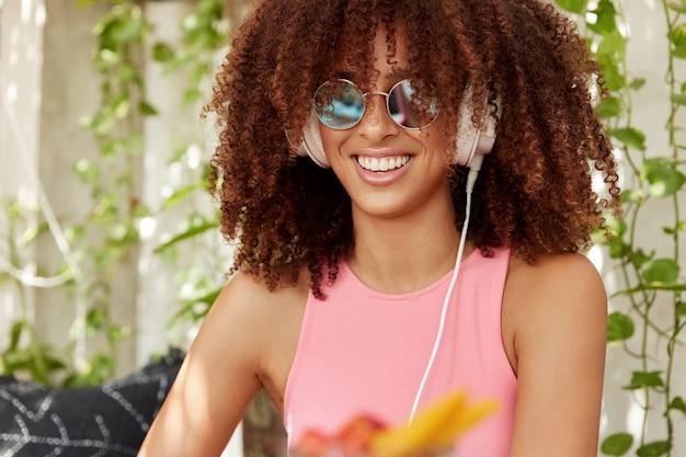 Innenaufnahme der schönen jungen frau mit afro-frisur, trägt trendige sonnenbrille, hört lieblingslieder allein in kopfhörern, hat strahlendes lächeln. sorglose dunkelhäutige frau lacht freudig