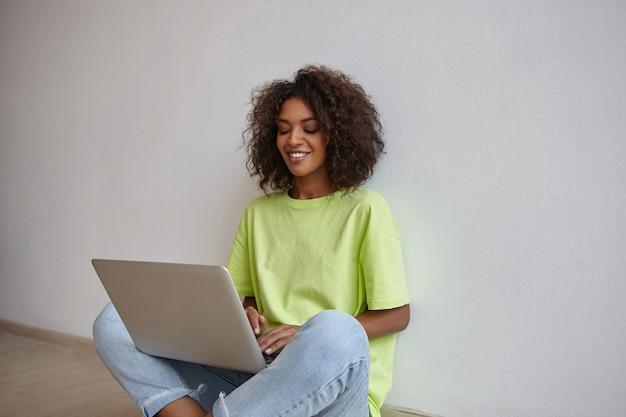 Innenaufnahme der schönen jungen frau mit der dunklen haut, die auf boden mit laptop sitzt, bildschirm mit aufrichtigem lächeln betrachtet und hände auf tastatur hält