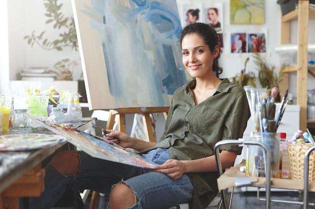 Innenaufnahme der schönen malerin, die hemd und jeans trägt, am stuhl sitzt, bunte öle mischt, pinselstriche auf staffelei macht. kunstliebhaberin, die das zeichnen in ihrer werkstatt übt