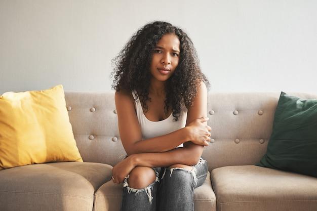 Innenaufnahme der schönen modischen jungen mischlingsfrau mit afro-frisur, die zu hause auf der couch sitzt, die stirn runzelt, traurigen blick besorgt hat, unter magenkrämpfen leidet oder sich einsam und verärgert fühlt