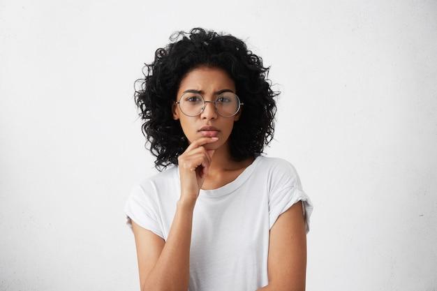 Innenaufnahme der schönen nachdenklichen jungen hausfrau der gemischten rasse