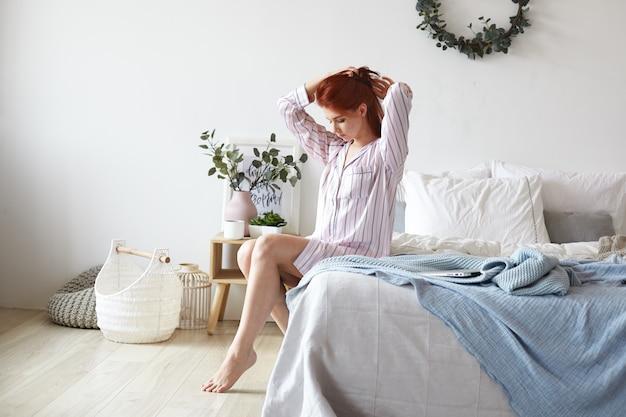 Innenaufnahme der schönen romantischen jungen frau, die gestreiften pyjamas trägt, sitzt auf ungeschminktem bett mit nackten füßen auf laminatboden, macht ihre haare, bereitet sich auf neuen tag vor. menschen- und lifestyle-konzept