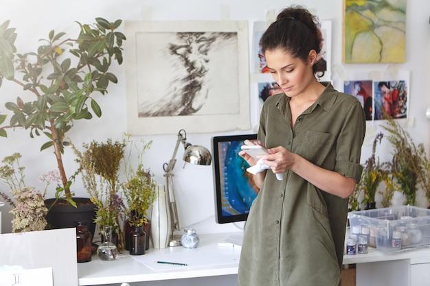 Innenaufnahme der schönen schönen brünetten jungen frau designer, die textnachricht auf handy, online-einkauf, bestellung von farbe, leinwand oder rahmen tippt. menschen, kunst, kreativität und technologiekonzept