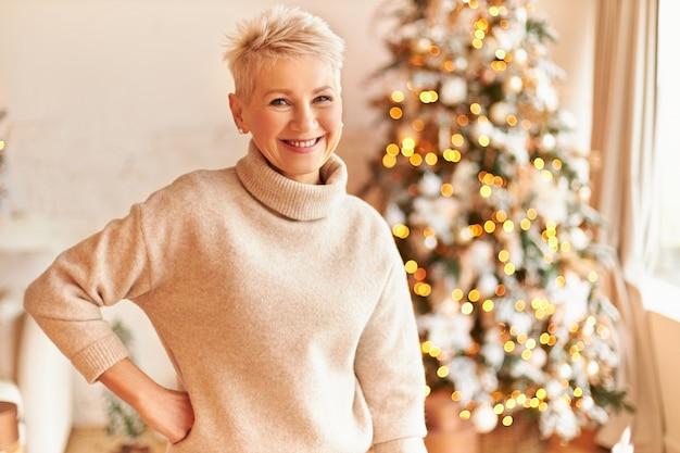 Innenaufnahme der schönen überglücklichen reifen frau mit blonden pixie-haaren, die am geschmückten weihnachtsbaum aufwerfen, kuscheligen pullover tragen, bereit zum feiern, lächeln und positive festliche stimmung haben