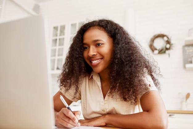 Innenaufnahme der selbstbewussten fröhlichen jungen dunkelhäutigen freiberuflerin, die am esstisch sitzt und entfernt mit tragbarem computer arbeitet. moderne elektronische geräte, job- und berufskonzept