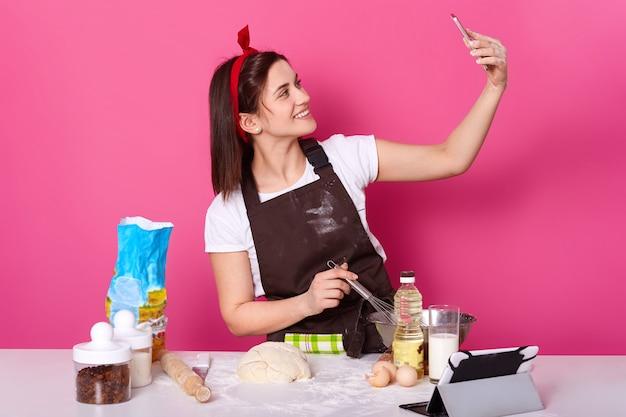 Innenaufnahme der stehenden lächelnden charismatischen jungen dame, die selfie in der küche macht, während sie neues köstliches gericht kocht, fotos und videos auf social-networking-sites veröffentlicht. back- und kochkonzept.