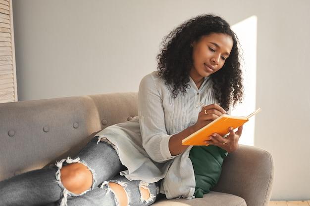 Innenaufnahme der trendig aussehenden jungen afroamerikanerin, die zerrissene jeans trägt, die auf bequemem sofa im wohnzimmer liegen und in tagebuch aufschreiben, einkaufsliste machen, bevor sie einkaufen gehen